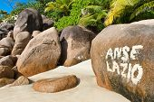 Painted sign on a rock for Anse Lazio, Seychelles, marking the idyllic tropical beach on the island with its golden sand and granite boulders