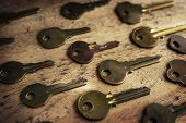 Various vintage brass keys aligned in the same direction on a old wooden desk. Security and encryption, concept image. High magnification macro.