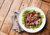 Salad Leaves With Sliced Roast Beef And Sun-dried Cherry Tomatoes On Wooden Background