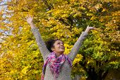 Carefree Young Woman Enjoying Autumn With Arms Raised