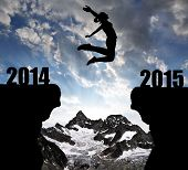 Girl jumps to the New Year 2015 in the background mount Ober Gabelhorn