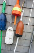 Colorful fishing buoys hanging on wall.