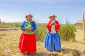 PUNO, PERU, MAY 5, 2014: Uros islands on Titicaca lake - Local women in traditional attire sing welcoming tourists visiting islands