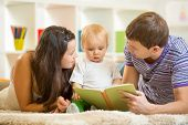Young parents mom and dad reading children book to baby boy