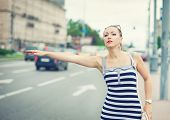 Young Beautiful Woman Trying To Hail A Cab In The City