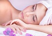 Closeup portrait of beautiful woman lying down on massage table, enjoying aromatherapy in luxury spa salon, healthy lifestyle concept