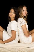 Two Women White Dress On Black Back To Back Serious