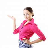Young cheerful woman pointing at copy space