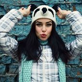 beautiful cool girl in funny hat against grunge brick wall make faces, toned
