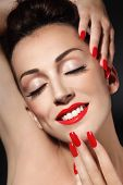 Portrait of young beautiful smiling girl with long red nails and lipstick