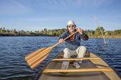 senior male enjoying morning sun on a lake in a canoe, Riverbend Ponds Natural Area, Fort Collins, Colorado