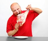 Angry hungry man eating raw bloody meat. Healthy eating concept.