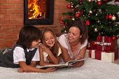 Family reading a story at Christmas time - spending time together by the fireplace