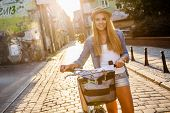 Young stylish woman with a bicycle in a city street