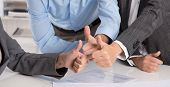 Concept for successful teamwork: business people making thumbs up gesture.