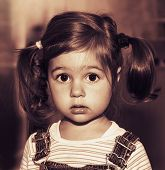 Portrait of cute sad little girl thinking. Toned