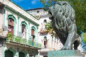 Bronze lion and historic buildings at El Prado Boulevard, a famous landmark in Havana