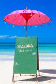 colorful pillows and bright umbrella on tropical sea and beach background, vacation in tropics, welcome sign to beach restaurant