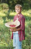 Portrait Of Standing Boy Holding Red Wildberries