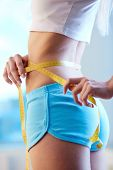 Close-up of slender woman measuring her waist after training