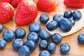 Blueberries on wooden spoon with strawberries
