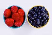 Blueberry and strawberry in white bowls