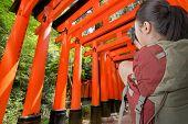 picture of inari  - Asian female backpacker take photo in Fushimi Inari Taisha - JPG