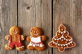 Christmas homemade gingerbread couple and tree on wooden table
