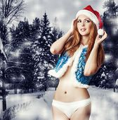 stock photo of mink  - Sexy woman santa claus in white pants blue vest with fur mink and red had in snowy forest - JPG