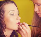 stock photo of makeup artist  - makeup artist is applying cosmetics on model face - JPG