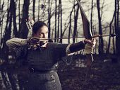 image of bow arrow  - Medieval archer woman she wearing a chainmail and use a bow and arrow gloomy forest cross - JPG