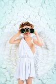 image of cupid  - Cute little boy in a costume of angel looking through the binoculars - JPG