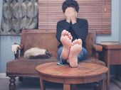 pic of settee  - A young man is resting his bare feet on a coffee table while he is sitting on a sofa with his head in his hands - JPG
