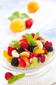 image of mints  - Fruit salad with mint in a bowl. Focus on raspberry and parts of mint leaves in the center of the bowl. ** Note: Shallow depth of field - JPG
