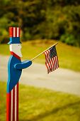 stock photo of uncle  - Wooden Uncle Sam waving an American flag - JPG