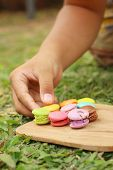 pic of picking tray  - Hand were picked colorful of macaron on a brown tray - JPG