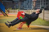stock photo of playground  - Young man reliving his childhood plying in a childrens playground riding on a colorful red spring seat with a happy smile in an urban park - JPG