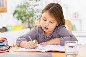 stock photo of homework  - Little kid at home doing homework - JPG