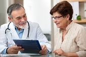 stock photo of observed  - doctor talking to his female patient at office - JPG