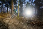 picture of dirt-bike  - Mountain biker riding his bike on a gravel dirt trail - JPG