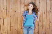 stock photo of dreadlock  - Stylish slim girl with dreadlocks on wooden wall background - JPG