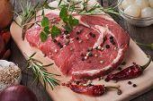 picture of ribeye steak  - Raw ribeye steak on wooden board with peppercorn and rosemary - JPG