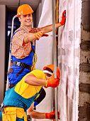 stock photo of millwright  - Two working men in builder uniform indoor - JPG