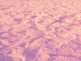 pic of footprint  - Sand on the beach with many footprints in gradiented pastel orange - JPG