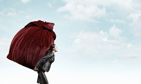 image of heavy bag  - Businesswoman carrying big heavy bag on back - JPG