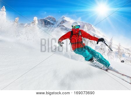 Skier skiing downhill during sunny