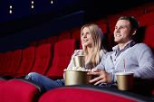 stock photo of movie theater  - Attractive young couple looking at a movie theater - JPG