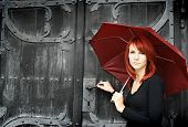 beautiful girl under rad umbrella near the old door