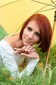 image of young girls  - beautiful girl relaxing on grass under yellow umbrella - JPG