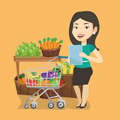 Young caucasian woman checking shopping list. Smiling woman holding shopping list near trolley with  poster